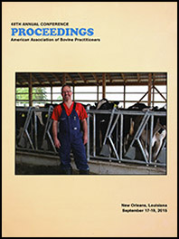 Cover image of the 48th Conference Proceedings: An image of Dr. Fred Gingrich II dressed in a red shirt and overalls and standing in front of dairy cows in a barn interior. Yellow background.